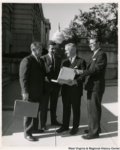 Congressman Arch A. Moore, Jr. holding a binder and discussing it with three unidentified men. The binder is the 'Comprehensive Plan for Paden City, West Virginia'.  The Capitol building is in the background.