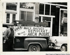 "A man standing by his truck, which has a sign on it stating, ""Look. Here's another Democrat voting for Arch Moore."""
