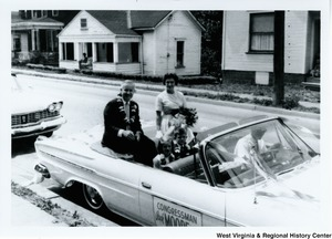 "Congressman Arch A. Moore, Jr. and his wife, Shelley, sitting on the back of a convertible car.  Arch is wearing a lei and Shelley is holding a bouquet of flowers.  Sitting in the back seat are their three children, Shelley, Arch (Kim), and Lucy. The side of the car says ""Congressman Arch Moore."""