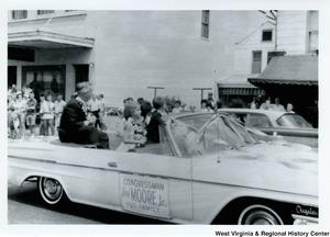 "Congressman Arch A. Moore, Jr and his family in the back of a convertible during a parade. The car has a sign on the side that says ""Congressman Arch Moore, Jr. and family."" The Moore's are all wearing flower lei's."
