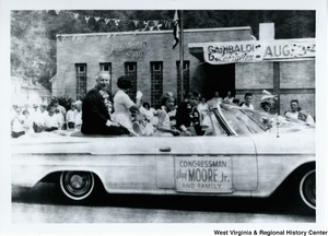 "Congressman Arch A. Moore, Jr. with his wife and three children in the back of a convertible during a parade. The car has a ""Congressman Arch Moore, Jr. and family"" sign on the side."