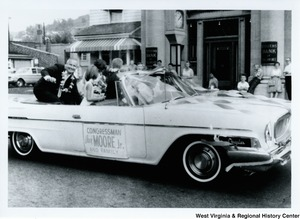"Congressman Arch A. Moore, Jr. and his family in the back of a convertible during a parade. Moore is raising his hand to wave. A sign on the side of the vehicle reads ""Congressman Arch Moore, Jr. and family."" The family members are all wearing flower lei's, except Mrs. Moore who has a bouquet."