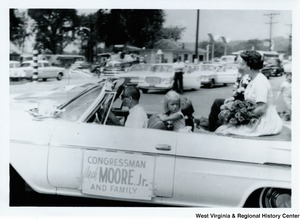 "Congressman Arch A. Moore, Jr. and his family in the back of a convertible during a parade. Mrs. Shelley Moore and their daughter Lucy, are shown. Mrs. Moore is holding a bouquet of flowers. Lucy is leaning against the back of the driver seat. A sign on the side of the vehicle reads ""Congressman Arch Moore, Jr. and family."""