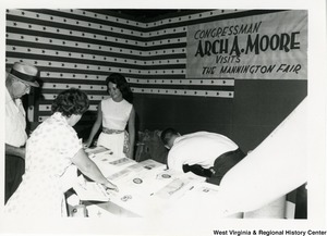 Congressman Arch A. Moore, Jr.'s booth at the Mannington Fair. The booth is being worked by two unidentified people.