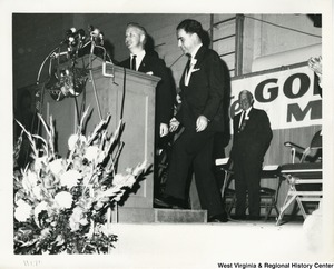 Governor Cecil H. Underwood walking up to a podium while Congressman Arch A. Moore, Jr. is standing beside him at a Goldwater/Miller rally.