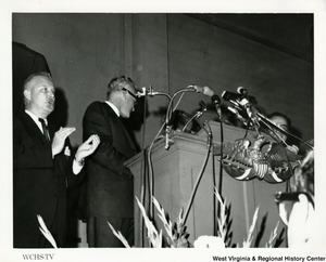 Congressman Arch A. Moore, Jr. standing beside a podium clapping. Presidential candidate Barry Goldwater is behind the podium.