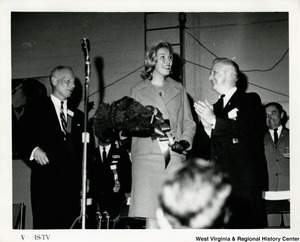 Congressman Arch A. Moore, Jr. clapping for an unidentified woman holding a bouquet at a Goldwater/Miller rally. An unidentified man is on the left side of the woman.