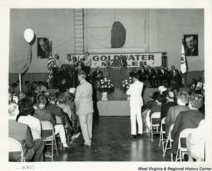 The audience and stage at a Goldwater and Miller presidential campaign rally. A band is playing on the left side of the stage and Congressman Moore and others are seated on the right side of the stage.