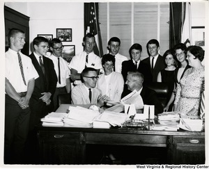 Congressman Arch A. Moore, Jr. seated at his desk surrounded by a group of young adults. He is holding the Congressional Record and talking to a man seated beside him.
