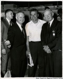 Congressman Arch A. Moore, Jr. standing with two unidentified men. There are people walking by behind them.
