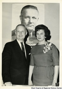 Congressman Arch A. Moore, Jr. standing with his wife Shelley. In the background is a political poster of Moore.