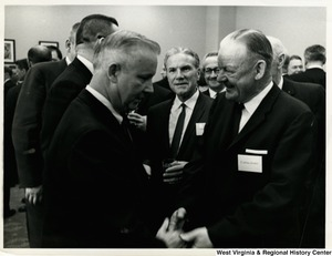 Congressman Arch A. Moore, Jr. going to shake the hands of a man, C. Wilson ?. A group of people are surrounding them talking.