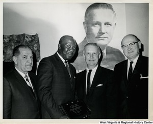 An unidentified man presenting Congressman Arch A. Moore, Jr. with an honorary plaque. Two other unidentified men are standing with him. In the background is a political poster of Moore.