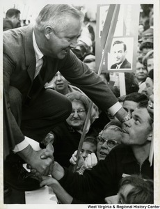 Congressman Arch A. Moore, Jr. crouching down to shake the hand of an unidentified man in the crowd during a Barry Goldwater rally in Wheeling.
