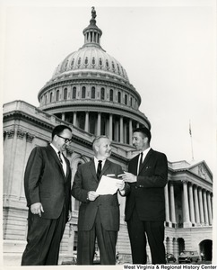 Congressman Arch A. Moore, Jr. showing a document to George Scott and Spencer (no other name given) in front of the Capitol.
