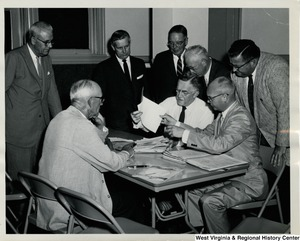 Congressman Arch A. Moore, Jr. and an unidentified group of men going over a stack of documents.