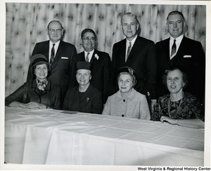 An unidentified group of four men and four women. The women are seated at a table while the men are standing behind them.