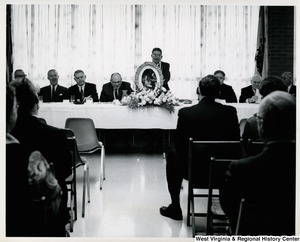 An unidentified man is speaking at a gathering. There is a photograph of a child with flowers surrounding him.  Congressman Arch A. Moore, Jr. is seated second from the left.