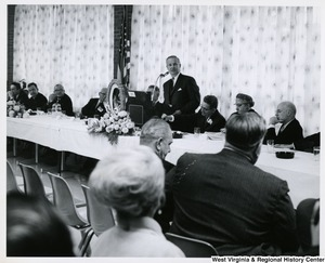 Congressman Arch A. Moore, Jr. standing at a tabletop podium speaking.  Seated at the table is a group of unidentified men. The photo is taken at an angle in the audience.