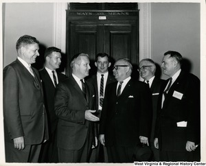 Congressman Arch A. Moore, Jr. with Herschel Perdue and an unidentified group of men. They are standing in front of the door for the Ways and Means Committee, room H - 208 in the Capitol.