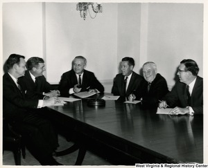 Congressman Arch A. Moore, Jr. sitting with a five unidentified men. They all have documents in front of them and appear to be discussing them.