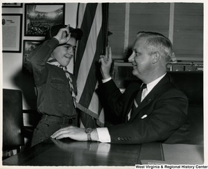 Congressman Arch A. Moore, Jr. being saluted by an unidentified Cub Scout.