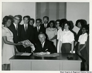 Congressman Arch A. Moore, Jr. with a group of student members of Moral Re-Armament. Moore is holding a copy of DARE (Drug Abuse Resistance Education) magazine.