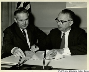 Congressman William M. McCulloch signing a document. Congressman Arch A. Moore, Jr. is sitting beside him.