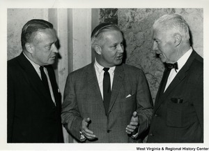 Congressman Arch A. Moore, Jr. (center) talking to two unidentified men.