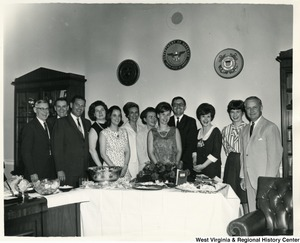 Congressman Arch A. Moore, Jr. standing behind a table of food with an unidentified group of men and women.