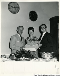 Congressman Arch A. Moore, Jr. (left) holding onto a glass plate along with an unidentified woman and man.