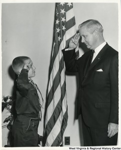 An unidentified Boy Scout saluting Congressman Arch A. Moore, Jr., who is saluting him back.