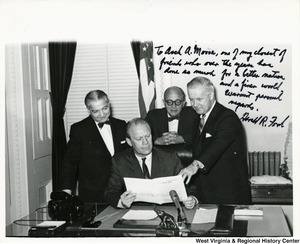 "Gerald Ford sitting at a desk looking at bill H.R. 2580. Congressman Arch A. Moore, Jr. is leaning over his shoulder pointing out something in the bill. Two other unidentified men are standing with Moore. The photograph is signed: ""To Arch A. Moore, one of my closest of friends who over the years has done as much for a better nation and a finer world. Warmest personal regards. Gerald R. Ford."""