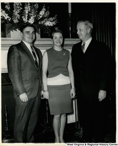 Congressman Arch A. Moore, Jr. (left) standing with Mr. and Mrs. Giovino J. D'Aurora in front of a fireplace.