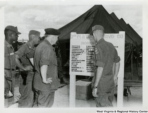 Congressman Arch A. Moore, Jr. with four others looking at the 3rd Platoon Bravo Company Honors board (Army).