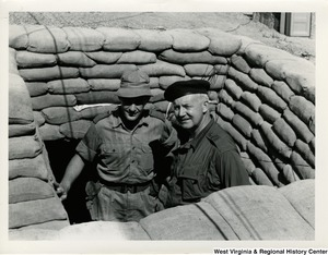 Congressman Arch A. Moore, Jr. standing in a foxhole in Vietnam with an unidentified man.