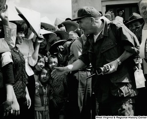 An unidentified man in uniform is reaching out to shake the hand of an unidentified Vietnamese woman in the Cau Xa Villiage.