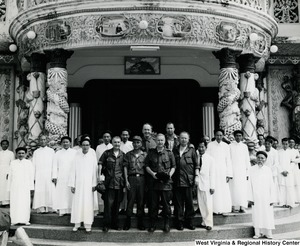 Congressman Arch A. Moore, Jr standing in front of the Cao Dai Temple in Tay Ninh, Vietnam with military personnel and temple workers.