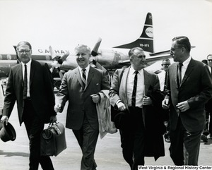 Congressman Arch A. Moore, Jr. and three unidentified men leaving their airplane after arriving in Saigon (Ho Chi Minh City), Vietnam.