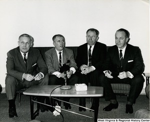 Congressman Arch A. Moore, Jr. (first on the left) sitting on a couch with three unidentified men waiting for a press conference.
