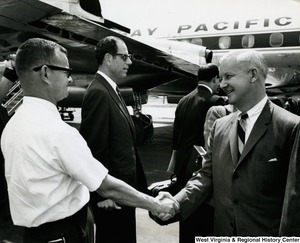 Congressman Arch A. Moore, Jr. shaking the hand of an unidentified man upon his arrival in Vietnam.