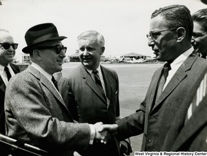 U.S. Operations Mission (USOM) Director Charles Mann welcoming Congressman Arch A. Moore, Jr. and two unidentified men to Vietnam. The Director is shaking hands with an unidentified man.