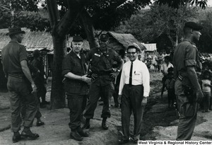 Congressman Arch A. Moore, Jr. talking to an unidentified man in a white dress shirt and a man in uniform. They are standing in a village or refugee camp in Vietnam.