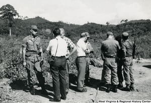 Eight unidentified men standing in groups talking in the Kon Tum Province, Vietnam.