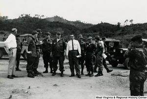 Congressman Arch A. Moore, Jr., standing second from the left, looking at an unidentified group of men in the Kon Tum Province of Vietnam. There is a jeep in the background.