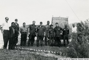 Congressman Arch A. Moore, Jr. (third from the right) standing with an unidentified group of men in front of a hut in Kon Tum Province, Vietnam.