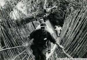 Two unidentified men crossing a narrow bamboo bridge in the Kon Tum Provience, Vietnam.  Another man in the background is just starting to cross the bridge.