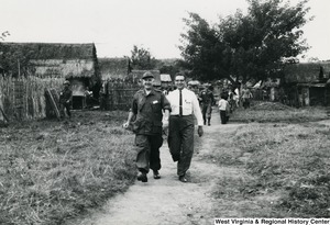 Two unidentified men walking through a village in the Kon Tum Provence, Vietnam.