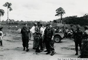 Congressman Arch A. Moore, Jr. standing with some unidentified men in uniform. There are Vietnamese people and a jeep in the background.