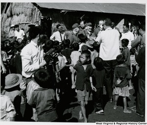 Congressman Arch A. Moore, Jr. with a group of unidentified men surrounded by children in Vietnam.